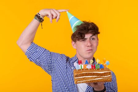 Positive funny young guy with a cap and a homemade cake in his hands posing on a yellow background. Anniversary and birthday concept. Reklamní fotografie