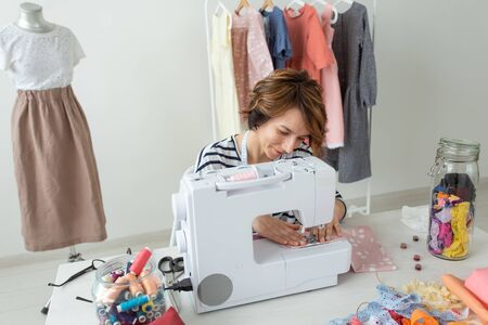 Young talented woman designer clothes sews her new product sitting at her desk with sewing machine and accessories. Concept of hobbies and professions. Фото со стока