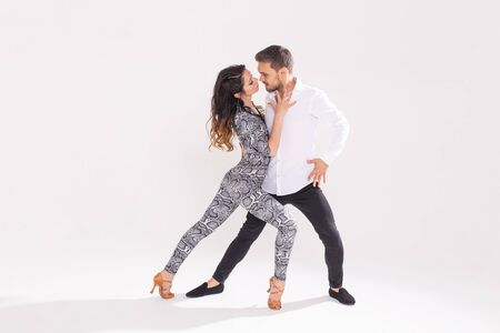 Young couple dancing over white background