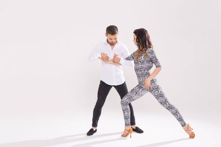 Skillful dancers performing in the white background with copy space. Sensual couple performing an artistic and emotional contemporary dance Фото со стока