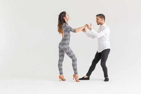 Young couple dancing latin dance bachata, merengue, salsa, kizomba. Two elegance pose over white background with copy space Фото со стока