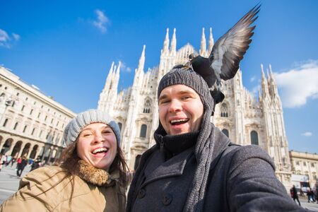 Travel, Italy and funny couple concept - Happy tourists taking a self portrait with pigeons in front of Duomo cathedral, Milan Reklamní fotografie