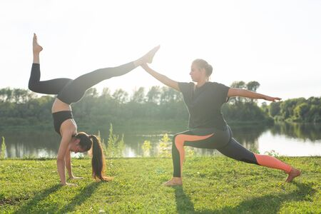 Healthy lifestyle and people concept - Flexible women doing yoga in the summer park Imagens - 132064808