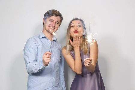 Party, new year, christmas and holidays concept - young couple holding sparklers on white background