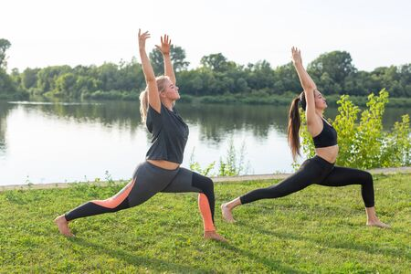 Healthy lifestyle and people concept - Flexible women doing yoga in the summer park Imagens - 132064663