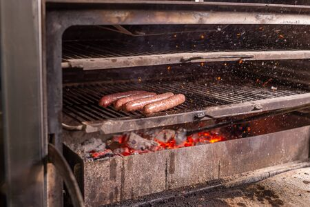 food, delicious and craft concept - grilled sausage on the flaming grill Фото со стока