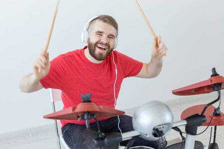 Drummer, hobbies and music concept - young man drummer in red shirt playing the electronic drums