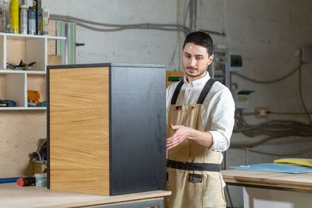 Furniture factory and small and medium sized enterprises concept - Man collects furniture details Imagens - 132064573