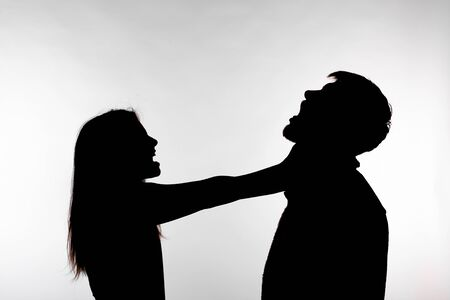 Domestic violence and abuse concept - Silhouette of a man asphyxiating a woman
