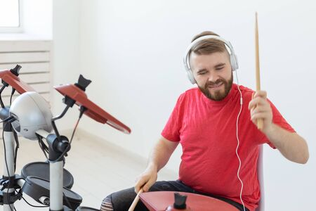 Hobby, music and people concept - Drummer man over the light background 写真素材