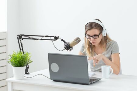Radio, dj, blogger and people concept - young woman presenter working on the radio studio and talking on the microphone