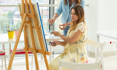 Art class and drawing concept - Woman artist working on painting in studio. Stock fotó