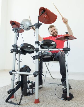 People, music and hobby concept - Tough man playing on electronic drum kit