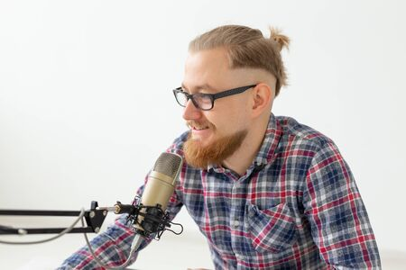 Blogger, streamer and people concept - Funny young man DJ working on the radio