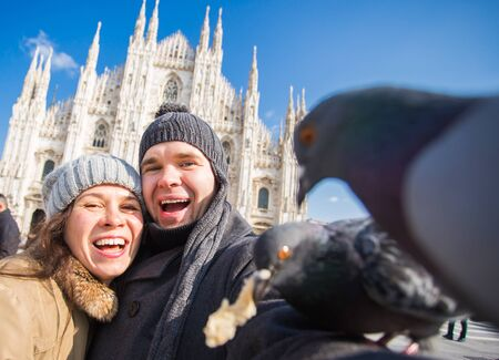 Travel, Italy and funny couple concept - Happy tourists taking a self portrait with pigeons in front of Duomo cathedral, Milan Stock Photo