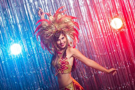 Carnival, belly dance and holiday concept - Beautiful female samba dancer wearing gold costume and smiling Standard-Bild - 131149097