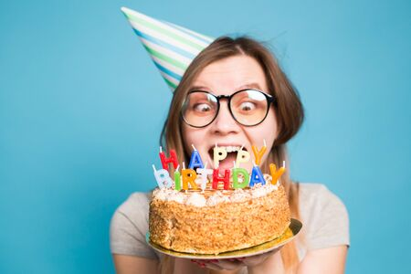 Crazy funny girl in a paper hat and glasses holding a big birthday cake on the blue background. Concept of prank and greetings.