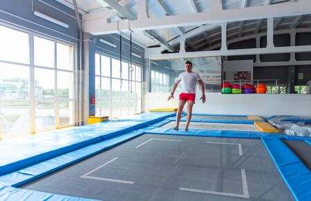 Fitness, fun, leisure and sport activity concept - Handsome happy man jumping on a trampoline indoors.