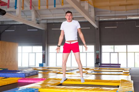 Leisure, sports games and interests - Funny young man trampolining in fly park