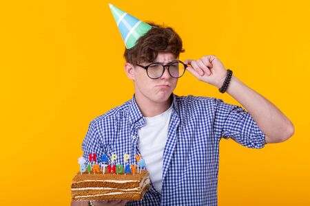 Funny positive guy holds in his hands a homemade cake with the inscription happy birthday posing on a yellow background. Concept of holidays and anniversaries.