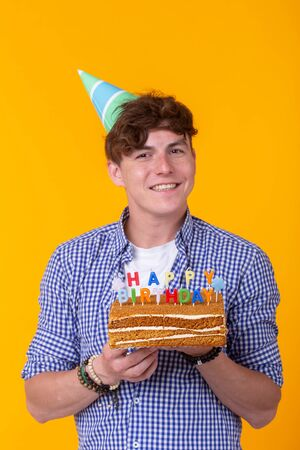 Positive funny young guy with a cap and a homemade cake in his hands posing on a yellow background. Anniversary and birthday concept. Stock Photo