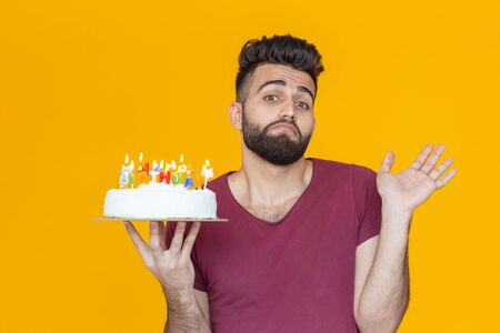 Positive funny young guy with a cap and a burning candle and a homemade cake in his hands posing on a yellow background. Anniversary and birthday concept.