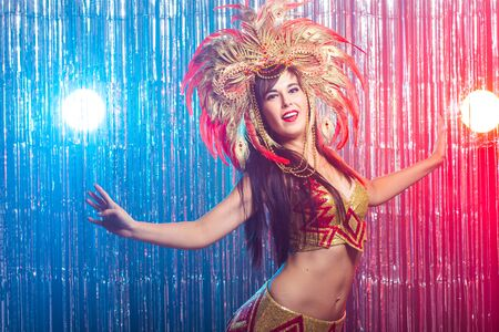 Carnival, belly dance and holiday concept - Beautiful female samba dancer wearing gold costume and smiling Standard-Bild - 131465410