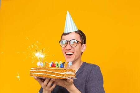 Positive funny young asian guy with a cap and a burning candle and a homemade cake in his hands posing on a yellow background. Anniversary and birthday concept.