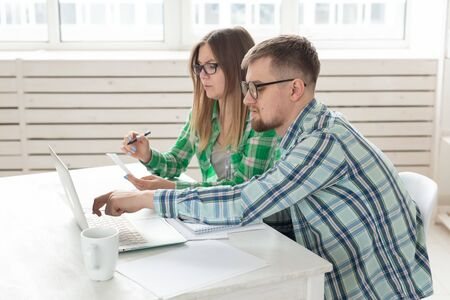 Husband and wife discuss amount in check for payment of the apartment and compare it with the rates on official website while sitting at the table with laptop