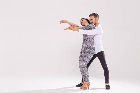 Social dance, bachata, kizomba, zouk, tango concept - Man hugs woman while dancing over white background with copy space