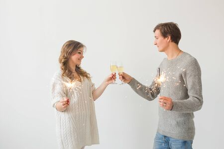 New year, holidays, date and valentines day concept - Loving couple holding sparklers light and glasses of champagne over white background with copy space