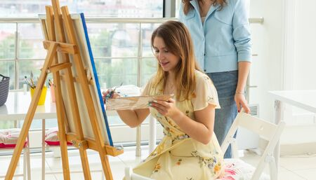 Art class, drawing and creativity concept - Close-up of female student sitting in front of easel with palette and paintbrush. Teacher helps her