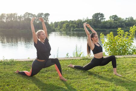 Small female fitness group doing yoga in park on a sunny day Фото со стока - 131390224