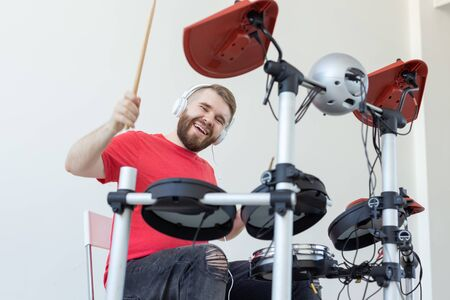 People, music and hobby concept - Happy man who spends his free time playing drums