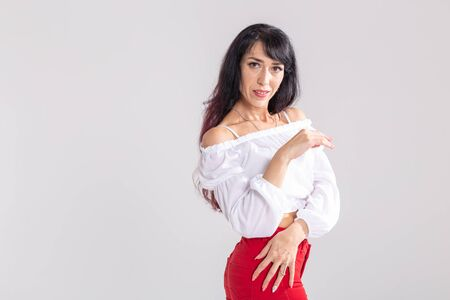 Latina dance, strip dance, contemporary and bachata lady concept - Woman dancing improvisation and moving her long hair on a white background with copy space