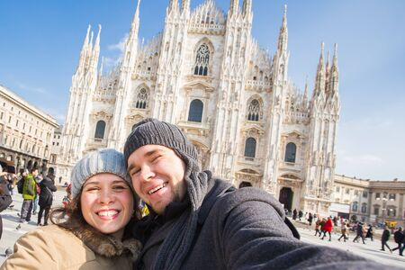 Funny couple taking self portrait in Duomo square in Milan. Winter traveling, Italy and relationship concept 免版税图像