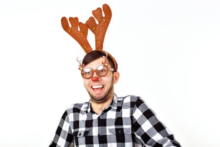 Christmas, holidays and funny concept - man with deer horns and rudolf nous on white background