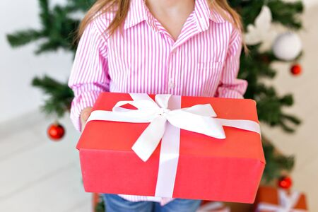 X-mas and holiday concept - Close-up of child with gift box on christmas tree background.