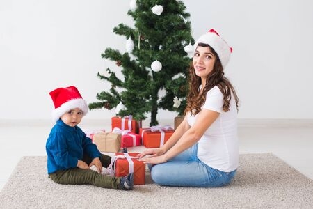 Christmas, single parent and holidays concept - Cute little boy holding christmas present for his mother at the home. Stock Photo