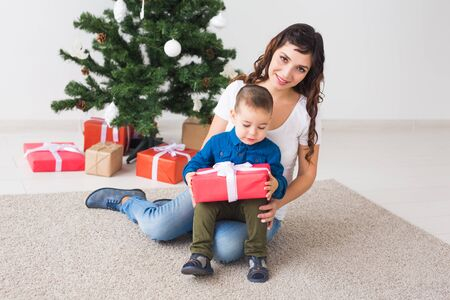 Christmas, single parent and holidays concept - Cute little boy holding christmas present for his mother at the home Stock Photo