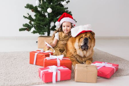 Children and pet concept - Cute girl with chow dog sitting near the Christmas tree. Merry Christmas and Happy Holidays. Foto de archivo - 133373053