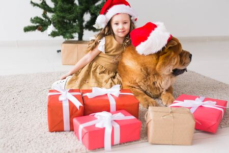 Children and pet concept - Cute girl with chow dog sitting near the Christmas tree. Merry Christmas and Happy Holidays. Foto de archivo - 133373055