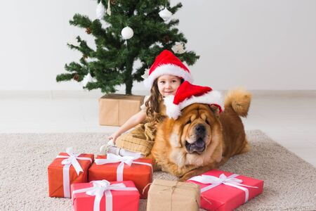 Children and pet concept - Cute girl with chow dog sitting near the Christmas tree. Merry Christmas and Happy Holidays. Foto de archivo - 133373056