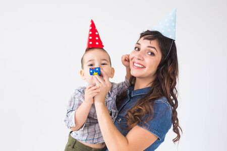 Family and holidays concept - Portrait of happy mother and baby at birthday party Stock fotó