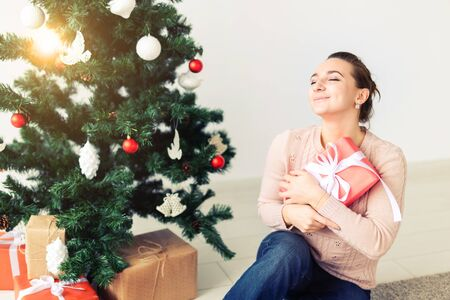 christmas, x-mas, winter, happiness concept - girl opens a gift against the background of the Christmas tree. Happy young woman celebrating Christmas Foto de archivo