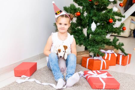 Christmas, pets and holidays concept - Child in santa hat with a jack russell terrier puppy