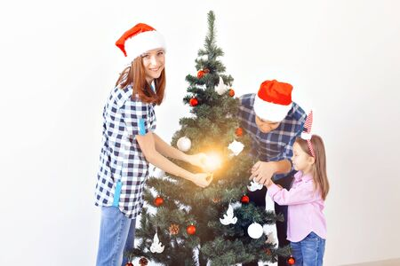 Holidays, x-mas and celebrating concept - Happy family decorating Christmas tree in holiday on white background 免版税图像