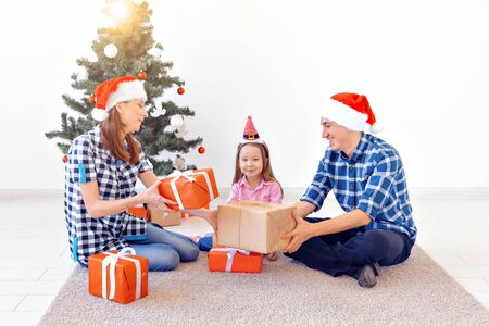 X-mas and holiday concept - Family opening christmas present in front of tree