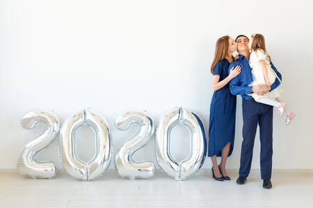 Young happy family mother and father and daughter standing near balloons shaped like numbers 2020 on white background. New year, Christmas, holiday