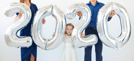 Young happy family mother and father and daughter holding balloons shaped like numbers 2020 on white background. New year, Christmas, holiday